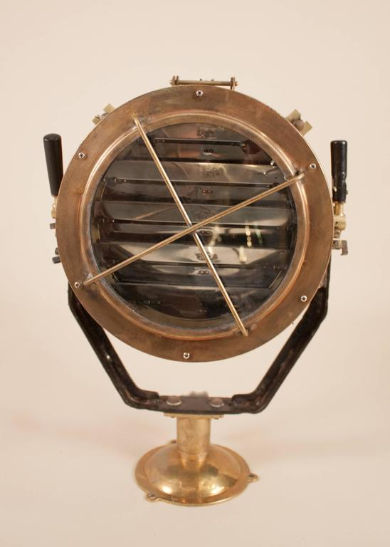 A solid brass daylight signaling lamp salvaged from a Japanese naval vessel and attentively restored. This mounted maritime spotlight features working aluminum signal shutters and sights, as well as multiple wooden levers/adjustments for