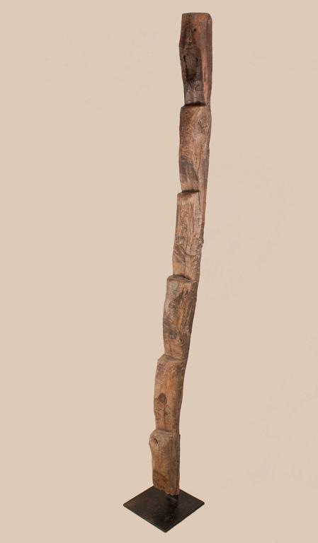 A late 19th century exotic hardwood ladder from Nagaland in Northeast India. This 7-foot functional sculpture features a primitively carved face with beard. The ladder is solidly mounted on a black iron base. Originally used to climb to raised