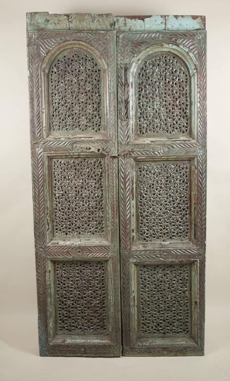 An exceptional pair of intricately hand-carved teakwood doors from India with pierced geometric and floral details. These exotic antique door panels feature original subdued green paint and iron latches.