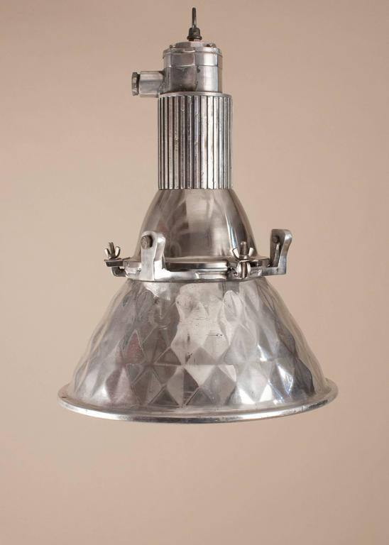 Mid-Century polished aluminum industrial or nautical spotlight with a pressed geometric pattern on both the outside and inside of the shade. The pendant's modest size makes it perfect in most any space. The light has been professionally restored and