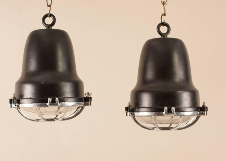 Very good-looking pair of aluminum and black powder-coated marine or industrial pendants, circa 1970. Manufactured for use on merchant vessels by Circle D of Carlstadt, NJ, the spotlights have weatherproof convex lenses protected by cast aluminum,