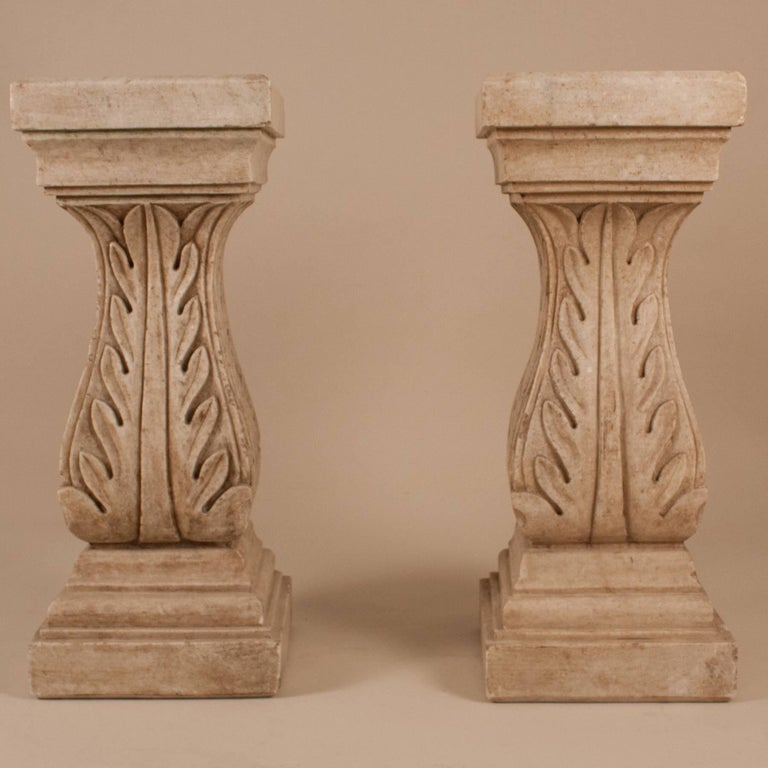 Pair of natural marble pedestals with carved acanthus leaves, circa 1950. Potential uses for these beautiful columns include as a console table base or as display stands for sculpture, etc.