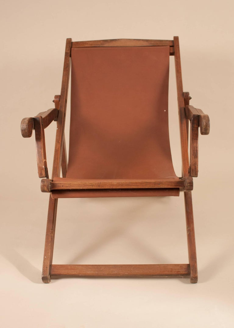 An authentic British Campaign folding, adjustable mahogany sling back chair, circa 1900, with its original wood finish. The plantation lounge chair's canvas sling was replaced some time ago with a chocolate-colored leather.