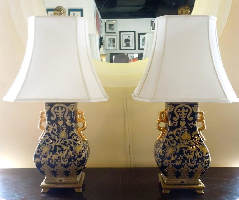 From the master bedroom of a very upscale Palm Springs estate, a chic pair of dark navy and gold ceramic chinioserie lamps. Beautiful gilt handles on each side of the urns. Antique gold wood bases. Obtain original chinioserie shades and Chinese