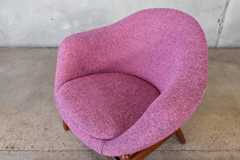 An uncommon lounge chair designed by Kofod-Larsen. A pod shaped seat created in foam sits over sculpted teak legs. A very unique look. This piece has been reupholstered in a fantastic vintage nubby fabric, it falls somewhere between pink and purple.