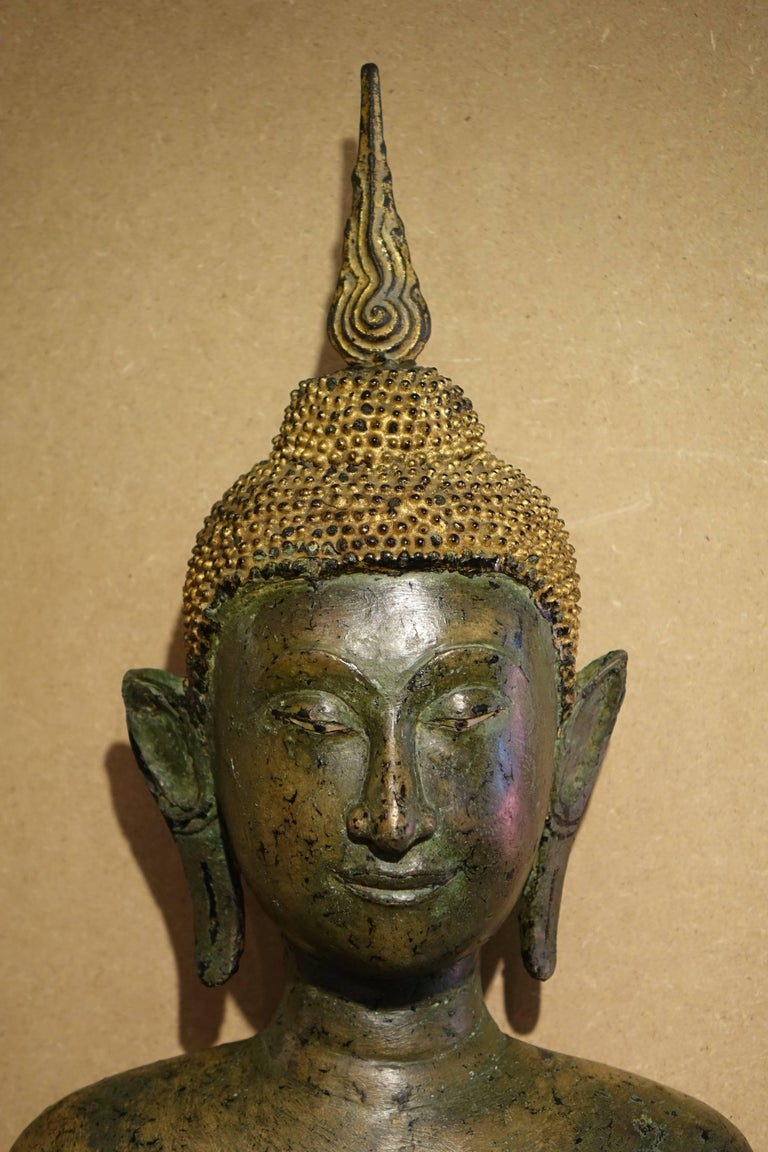 Ayutthaya style, bronze figure of Buddha 17th century, standing in samabhanga, both hands in Abhayamudra, wearing long cloak covering both shoulders, his face with downcast expression,, aquiline nose, smiling lips, elongated earlobes, curled