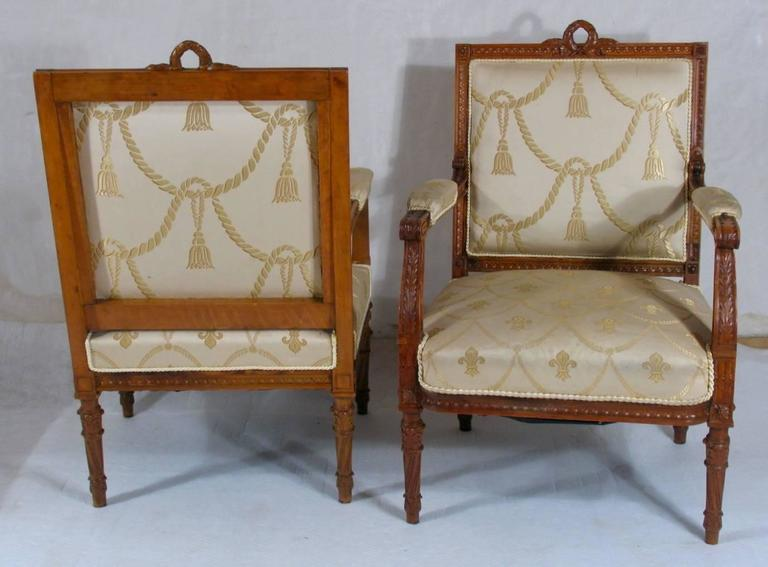Elaborate pair of Louis XVI-style fauteuils, finely carved pearwood. Straight back crowned with wreath, upholstered seat and back, ending on round tapered baluster legs. Originally the fauteuils belonged to a salon suite composed of one settee and