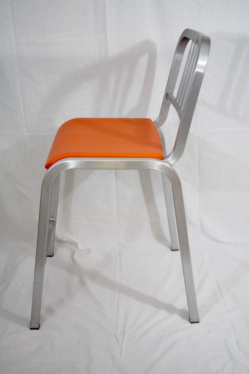 Pair of Emeco bar stools designed by Ettore Sottsass (1917-2007), brushed aluminum with orange plastic seats.