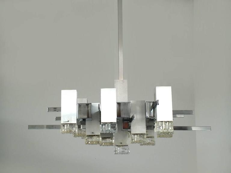 Sculptural extra-large Mid-Century Modern fixture designed by the Italian designer and manufacturer Gaetano Sciolari in the 1960s. An impressive geometrically shaped thirteen-light polished chrome and brushed aluminium chandelier with textured glass