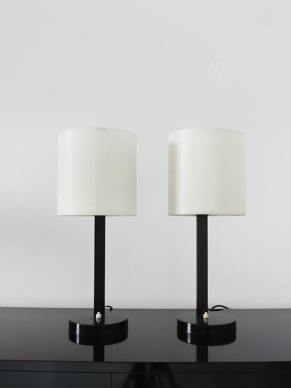 An absolutely stunning and rare pair of French Midcentury Modern table lamps in the style of Mathieu Matégot. Delicate white perforated metal shades and black colored bases. High quality, sturdy and heavy lamps with original switches. When lit, the