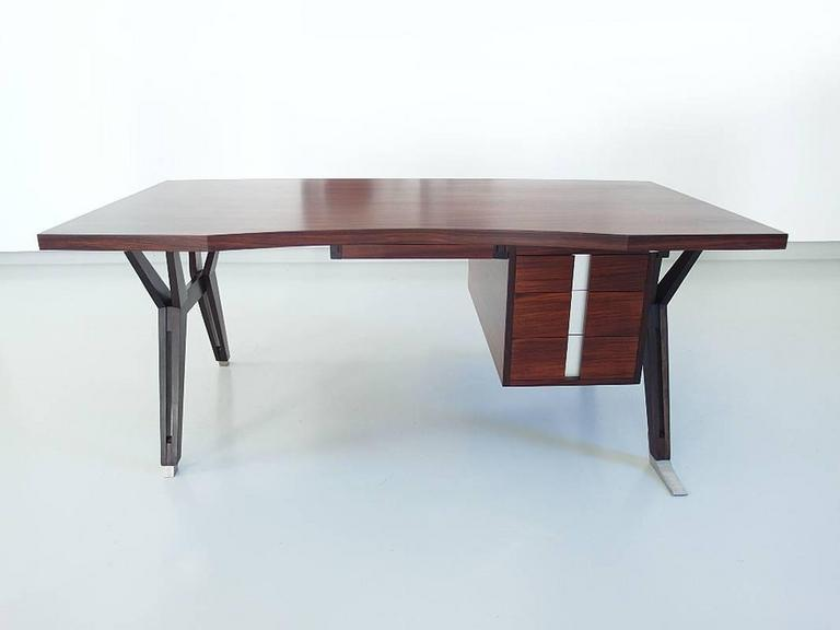 A stunning Terni executive desk designed by Ico Parisi in 1958 for MIM (Mobili Italiani Moderni), Rome, Italy. This elegant executive desk is made of beautifully grained hardwood with aluminium details. The curved desktop is floating above the solid