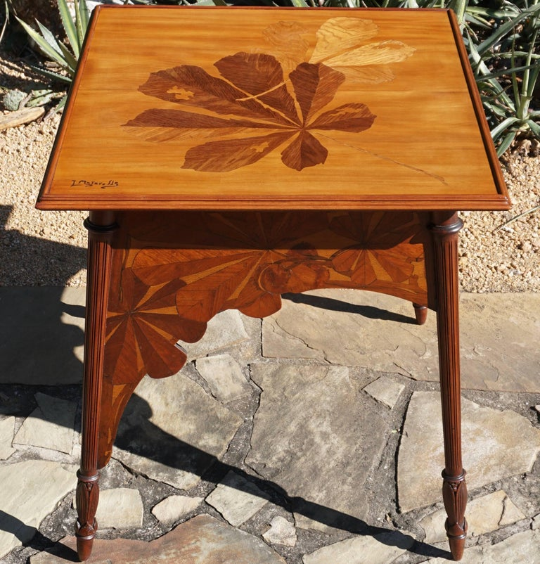 A French Art Nouveau marquetry walnut and exotic wood game table signed by Louis Majorelle. The tabletop is decorated with large leaves and stems. Stylized with fine marquetry side aprons support hand-carved legs, circa 1900. 
