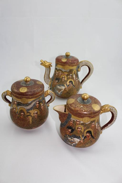 From the Richard (Dick) Bass estate.  Finely painted Japanese Satsuma porcelain dragon and immortals tea set from the Meiji period (1868-1912). The set consists of a teapot, sugar pot, milk pot, three lids, six cups and six saucers. 18