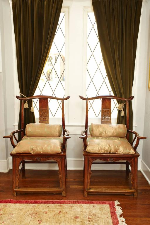 Late 18th-19th century elmwood armchairs, Ming style.  Each has a curved crest rail supported on curved rear posts and an S-shaped back splat. The arm rails are supported on slender standing stiles and extend beyond the front posts. The rectangular