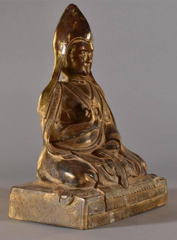 A Sino-Tibetan gilt bronze seated figure of a lama, Tsongkhapa, Chinese Qing dynasty, 18th century.  The large and magnificent figure is seated on a rectangular pedestal base with legs crossed in dhyanasana, one hand held in vitarka mudra and the