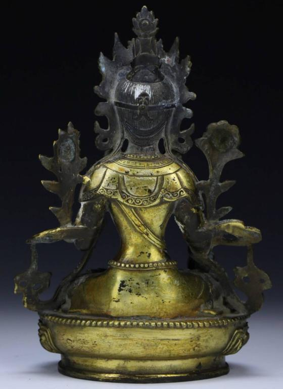 A gilt Tibetan bronze Buddha or Tara, seated with on hand raised and the other holding a sceptre. Original sealed base with rattling contents and Ming Yin/Yang symbol seal. Qing Dynasty.  Height: 8.5 Inches Width: 6 Inches  Condition: Some loss to