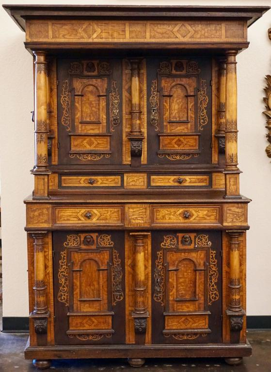 18th-19th century Alsacienne inlaid cabinet, the stepped inlaid cornice on columnar supports over two doors with architectural panels surmounted by putti masks above similar two-door base, upper and lower sections revealing shelved interiors, raised