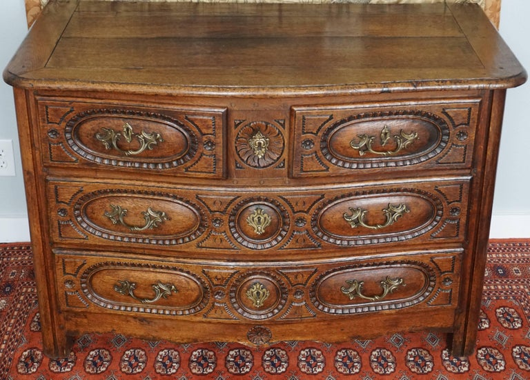 Louis XIV-XV French 18th century commode chest, 18th century, French Provincial oak four-drawer commode with bow serpentine front and carved drawer fronts.  Measure: 31.5