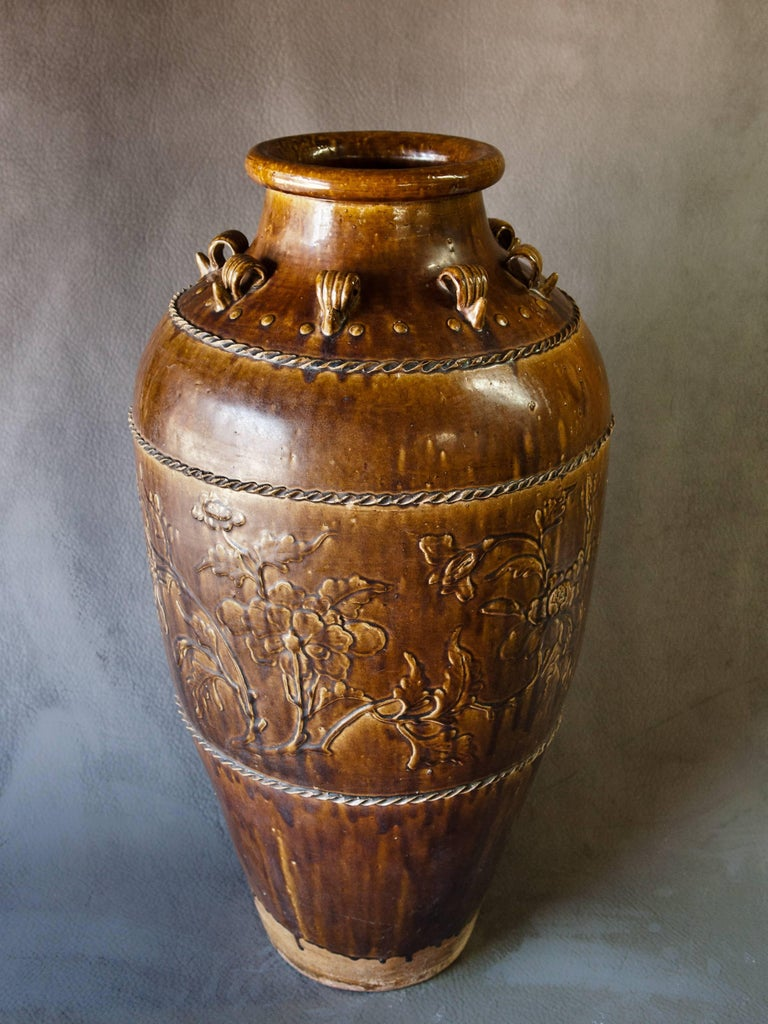 Tall Martaban ware storage Jar Ming dynasty found in Laos. Floral Design. Tall brown glazed storage jar found in Laos but manufactured in southern China most probably during the Ming Dynasty. The jar is in excellent condition with a floral design