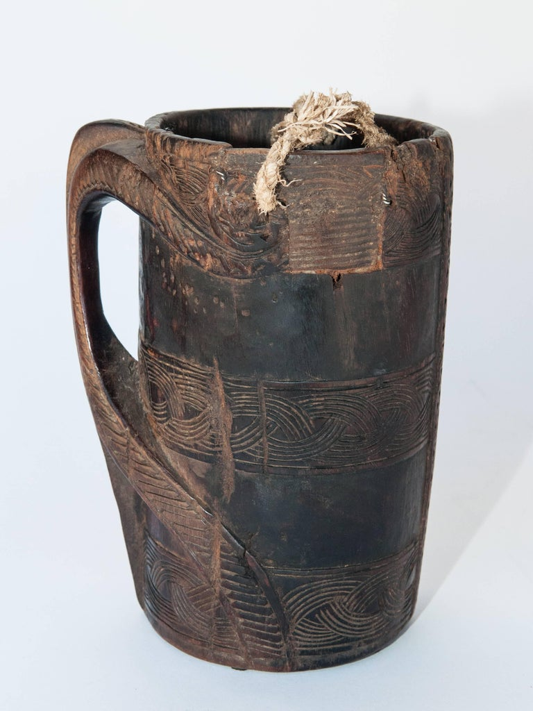 Wooden Carved Milk Pot with Stylized Monkey Motif. Mid-Late 20th Century. From the Middle Hills of West Nepal. This rustic milk pot was hand carved of local hardwood in the middle hills of western Nepal,  using very basic tools. Geometric designs