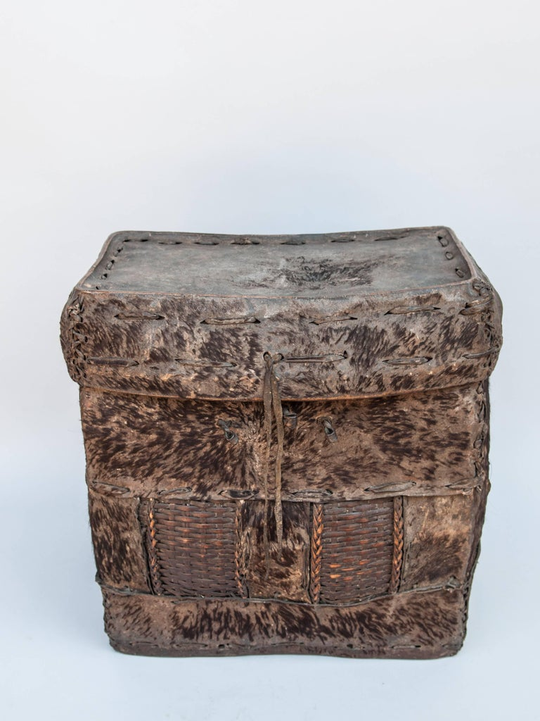 Tribal Storage Basket with Lid. Bhutan. Early to Mid-20th Century. Hide & Bamboo.  A handwoven rugged bamboo frame covered with hide, comprises this extremely robust rustic storage basket from Bhutan. This basket would have been used to store and