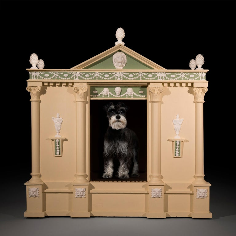 A very unusual, large and fine architectural dog kennel, modelled as a neoclassical temple, Possibly English, circa late 19th - early 20th century.  Of architectural form, with pineapple finials andlion mask mountedpediment, above the festive