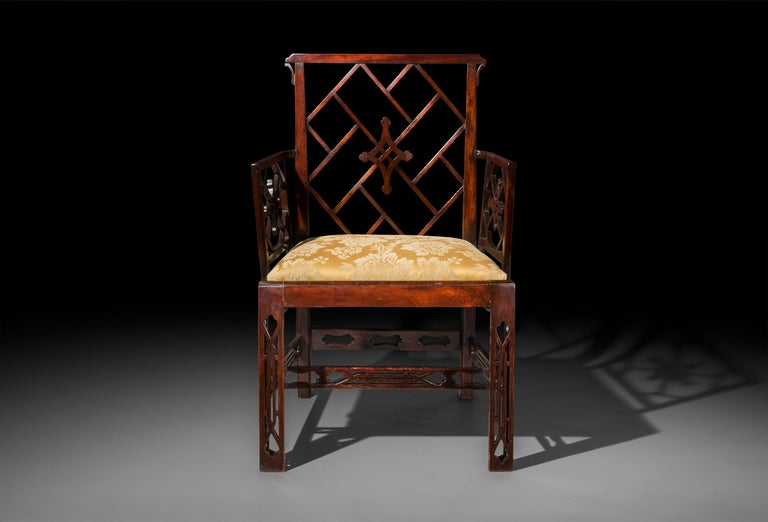 A generously proportioned George III period Chinese Chippendale mahogany armchair, after a design by Mayhew & Ince, circa 1760. Four armchairs available.  With a piercedgeometric back betweenconforming lattice armrests,above drop-in seats,