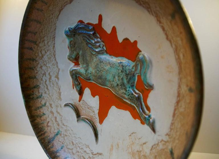 Massive and beautifully glazed stoneware bowl with 'jumping horse' centre motif executed with 'Verdigris green' glaze on a 'splatter' of red glaze. Designed by Swedish ceramist John Anderson (1899-1969) in the 1950s and manufactured by Höganas. A
