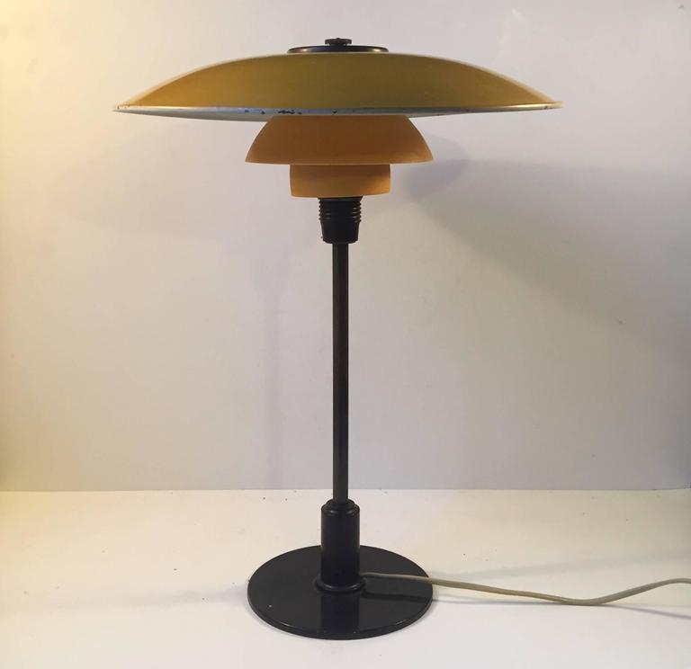 PH 3½-2 desk light by Poul Henningsen. Original yellow lacquered zinc top-shade, matté yellow single layered glass middle and bottom shade, patinated brass stem and Bakelite detailing. Manufactured by Louis Poulsen in Denmark circa 1930. Fine