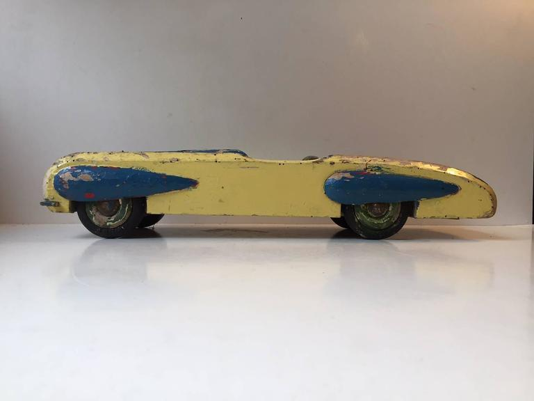 Large painted wooden Toy car with a lot of ware and personality. Numerous Worm-holes, several areas where the paint has worn off, a lot of scratches and scuffs - all around. Although it is mounted with Dunlop Tires this toy car is handmade in