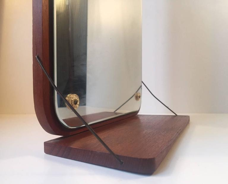Simple designed teak framed mirror with floating/brass suspended Shelf (26 x 10 cm). It was manufactured and designed in Denmark during the 1960s by Aarhus Glasimport & Glassliberi - design/size: No. 12. Very suitable as bedroom, bathroom or