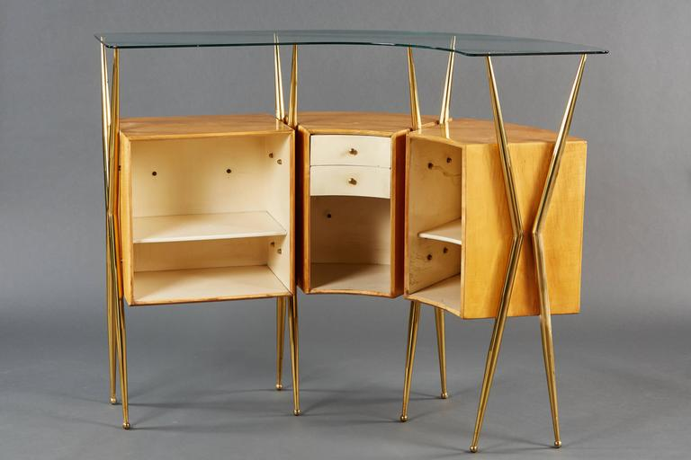 An elegant Italian bar cabinet, featuring a curvilinear design, mounted scenic illustrations and tapered brass legs.
