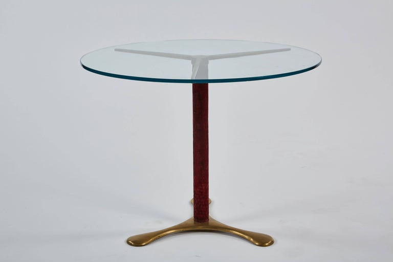 A delicate circular side table by Paolo Buffa, its glass top resting on a base of brass with a central upright in burgundy velvet.