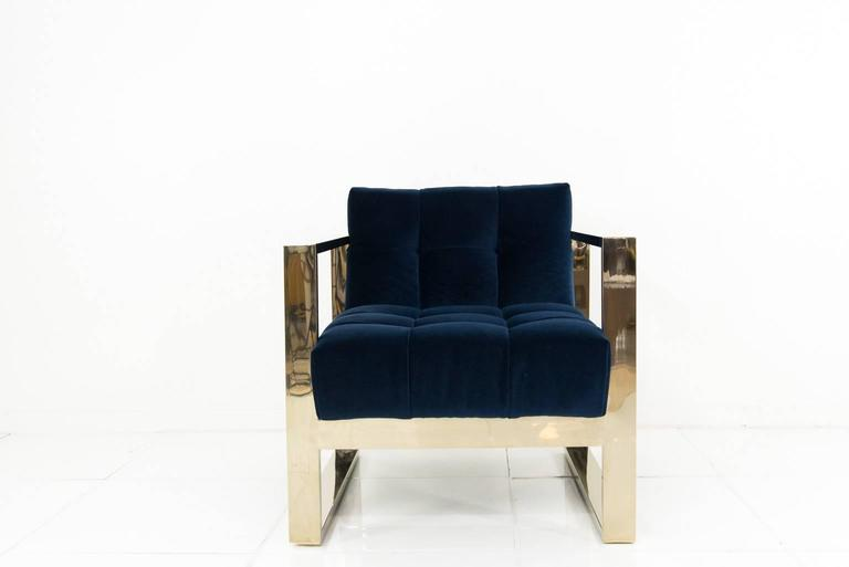 Modshop's wonderfully comfortable yet striking Kube chair with the all tufted back and tight seat. Finished in navy velvet and a brass U-leg frame.