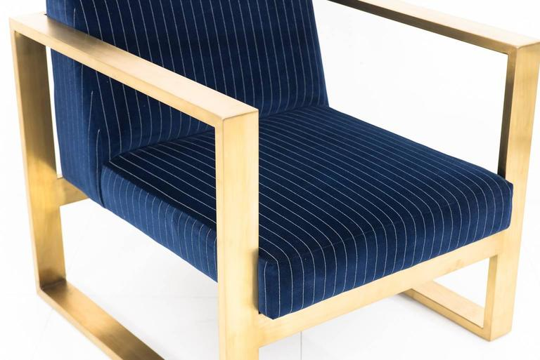 Modshop's Kube chair creates a stunning and comfortable tight seat chair. This is finished in navy pinstriped velvet and brass U-leg frame.