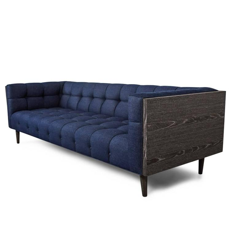 This sofa is a nod to Classic Mid-Century Modern design. A tight, tufted back and seat makes for an extremely sleek sofa. Encased in a dark walnut frame with matching cone legs, this a perfect piece to have floating in the middle of the room to