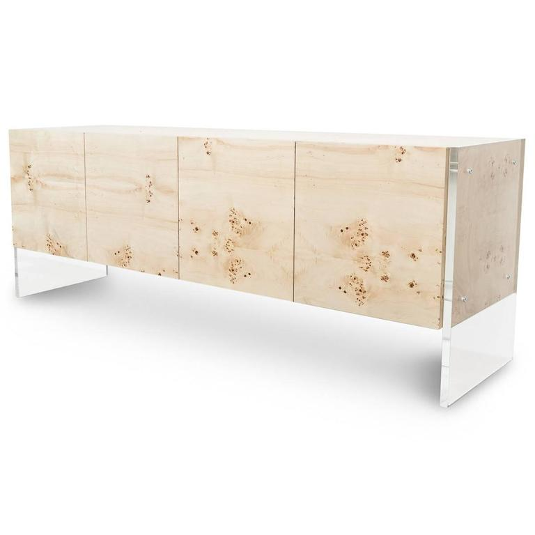Mid-Century styling meets modern design with our new Credenza. This four door piece is wrapped in a beautiful Burl wood veneer and stands on large Lucite plinth legs that run the height of the credenza along the outside edges. The credenza stands 9