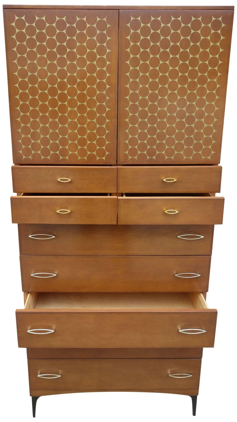 Said to be produced for only one year in 1959, the Contessa Line was a strong departure from the blonde wood they are known for. Featuring cherry brown finish with gold accents on metal legs. This rare midcentury wardrobe features four smaller