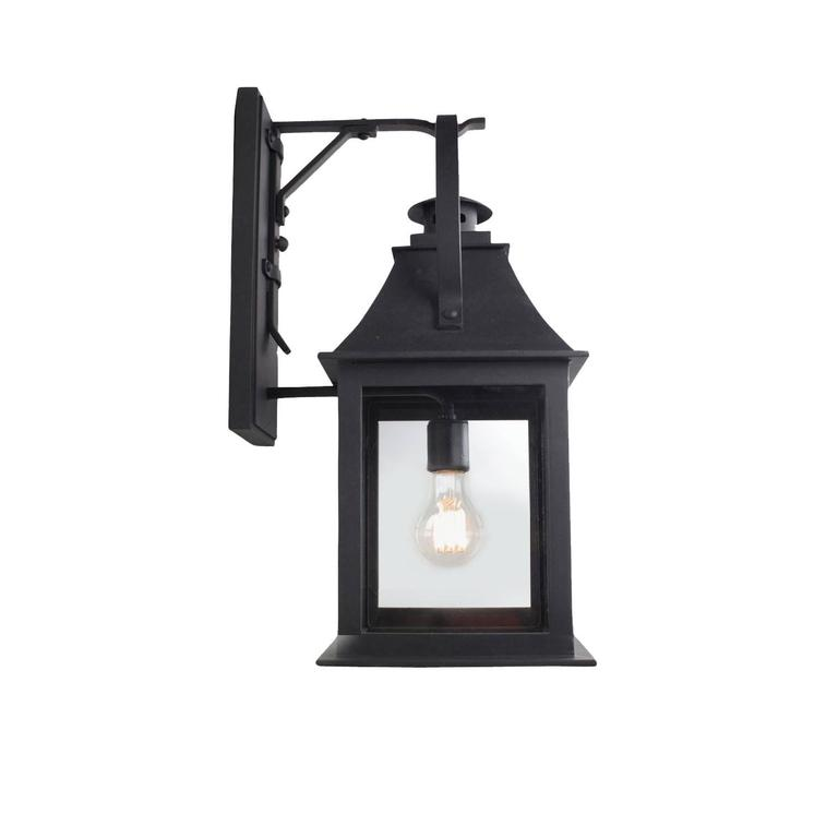 This lantern references both old and new with Classic features including a stove pipe top and oversized hoop, juxtaposed with modern lines and open glass panels. Hand-forged in heavy gauge iron.  All lanterns go through a metalizing process, a