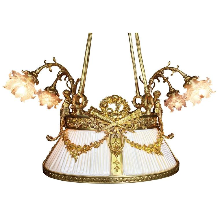 A fine and rare French 19th-20th century Belle Époque gilt bronze figural nine-light chandelier. The ovoid shaped frame, in the form of a hanging shade, surmounted with a gilt bronze Putto at each end, both holding floral wreaths below a two-light