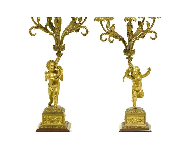 A very fine pair of French 19th century Louis XV style figural gilt bronze and rouge marble six-light candelabra, each with a figure of a standing cherub holding the ornate scrolled arm candelabra, crowned with a gilt bronze candle snuffer in the