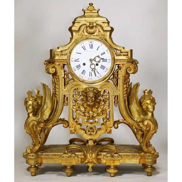 A very fine and palatial French 19th century Louis XIV style figural ormolu three-piece clock and candelabra garniture suite, comprising of a gilt-bronze clock and a pair of ten-light candelabra. The finely chased gilt-bronze clock with a domed top,