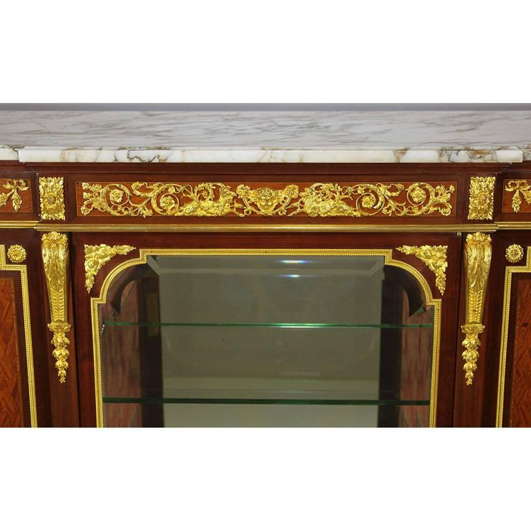 A very Fine French 19th-20th century Louis XVI style ormolu-mounted kingwood parquetry three-door vitrine commode with two centre glass shelves with mirror back and a Brêche Violette marble Top, attributed to François Linke. Stamped FL twice on the