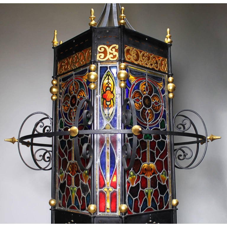 A palatial Italian 19th century Baroque style wrought iron and Vitreaux stain glass paneling entry eight-light grand hall lantern. The square black painted and parcel-gilt iron frame with flat corners, surmounted with a circular and a scrolled