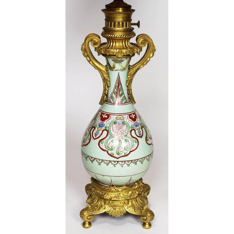 A fine pair of Chinese Export, 19th century porcelain bottle vases mounted with French ormolu as oil lamps. The well potted ovoid porcelain pear-shaped body decorated with hand-painted asymmetrical and floral designs in pale-green, red, light-blue
