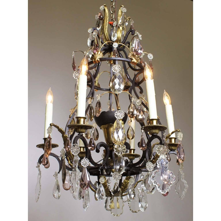 A French 19th-20th century Louis XV style wrought iron and bronze seven-light color crystal (cut-glass) chandelier. The black painted iron frame with six candle arms and a center light inside a cups, some of the pendants and drops are in amethyst