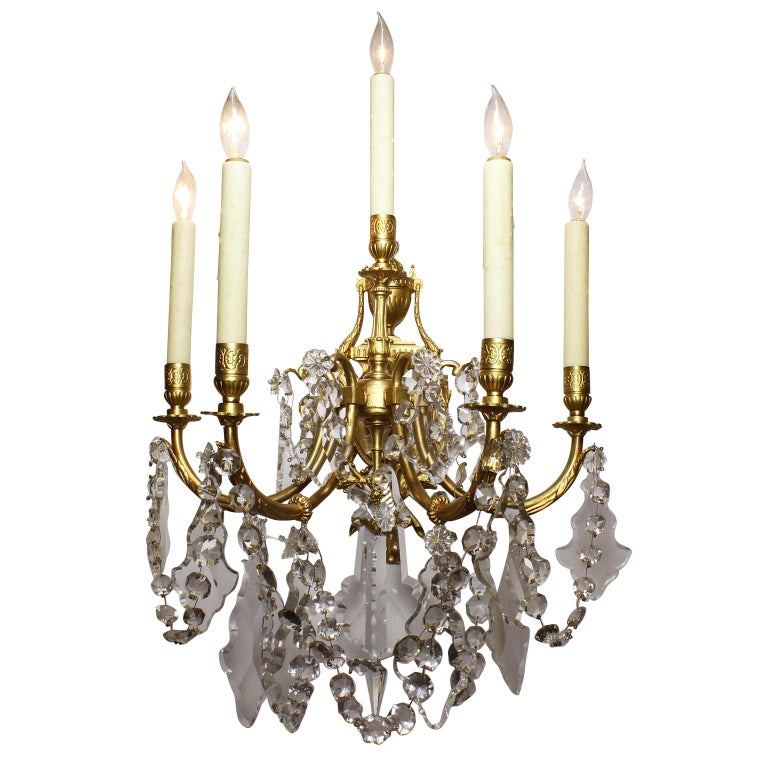 Pair of French 19th-20th century Louis XV style gilt-bronze and cut-glass five-light wall lights sconces. The shield-shaped back-plate crowned with an urn and surmounted with five scrolled candle arms, Paris, circa 1900.   Measures: Overall height