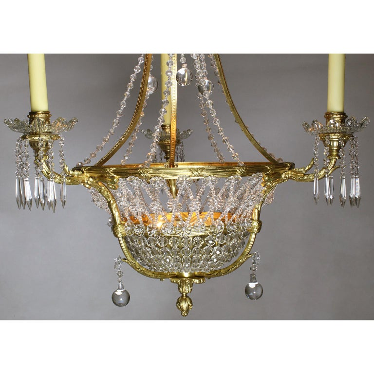 A fine French Belle Époque 19th-20th century three-light gilt-bronze and cut-glass basket chandelier. The circular basket shaped banded gilt-bronze frame surmounted with three scrolled candle-arms and two interior lights, all decorated with weaved