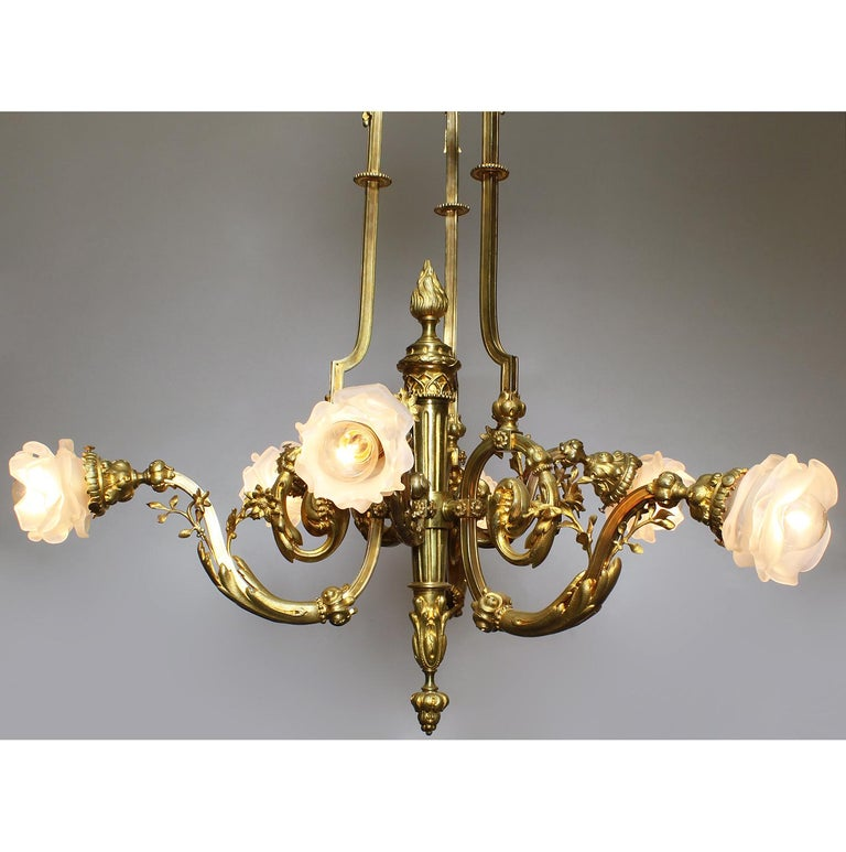 A fine French Louis XV style Belle Époque gilt bronze six-light chandelier. The Empire Revival gilt-bronze frame with a torch-shaped center stem with six scrolled arms fitted with frosted glass floral shaded, all crowned with a domed top surmounted