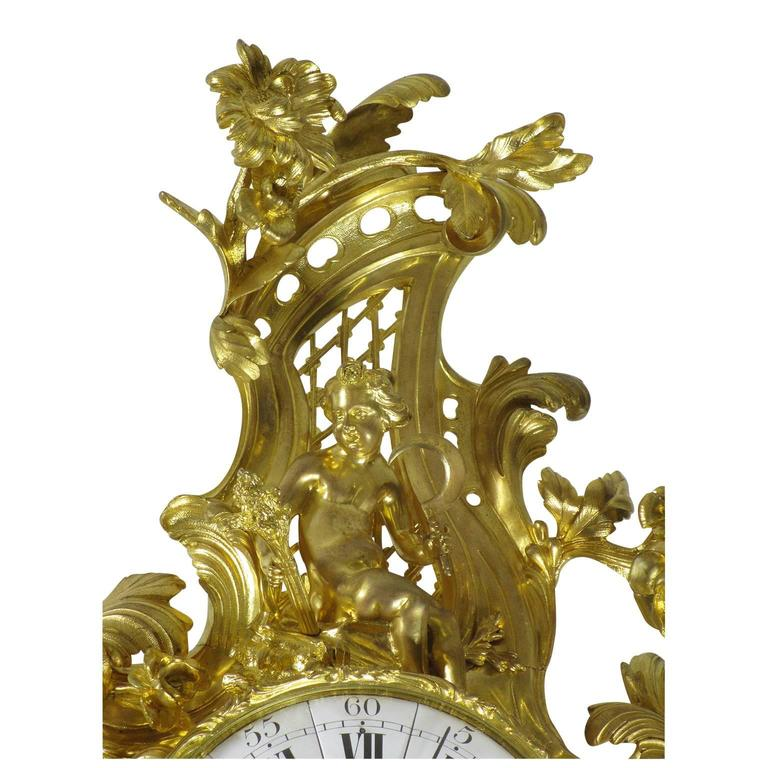A very fine and Palatial French 19th Century Louis XV Style gilt bronze figural cartel clock by Lerolle Frères, the finely frame body with a circular face with Roman numerals, the center with a profile of King Louis XV and inscribed Lerolle